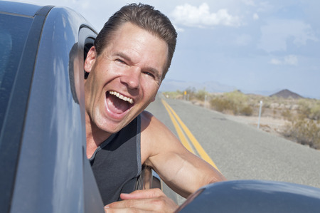 he laughs: Closeup of handsome free Caucasian man driving car with head out window down desert road as he laughs with extreme excitement