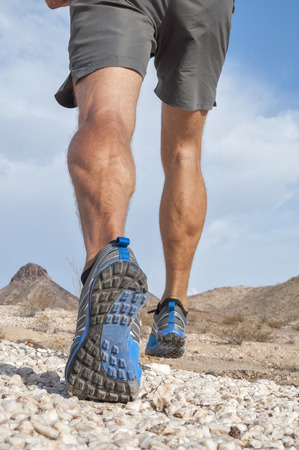 hamstring: Closeup of male runner wearing rugged trail running shoes as he runs away from camera over rocky desert landscape