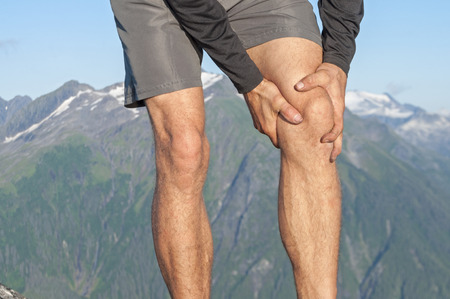 Closeup of male runner holding injured knee as he stands on scenic mountain top with snow capped peaks
