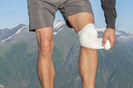 inflamation: Male runner wearing shorts on top of mountain with beautiful scenic view wraps injured knee with white sports bandage