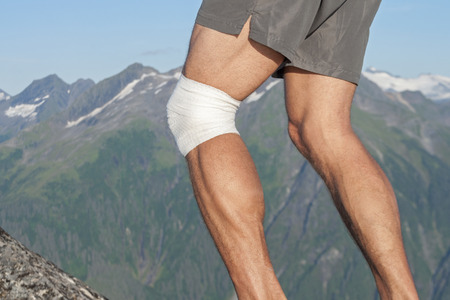legs around: Closeup of legs of male runner with white sports bandage wrapped around injured knee in beautiful scenic mountain landscape