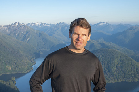 Caucasian male hiker in black shirt stands on top of mountain with beautiful scenic view of bay and mountains of Baranof Island in Alaska Stock Photo