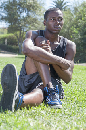 warm up: Athletic African American man stretches leg and glute muscle on park grass as he gazes away from camera