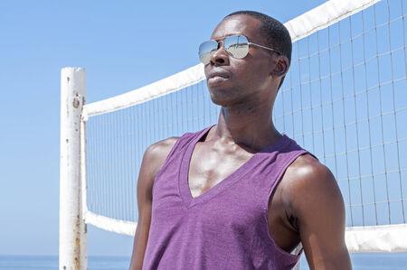 pelota de voley: Hombre americano joven hermoso africano que mira fresco y un estilo de tonos y la parte superior del tanque por red de voleibol en la playa en verano
