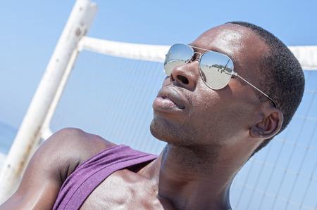 pelota de voley: Joven hombre americano estilo de moda africano hermoso en sombras frescas en frente de la red de voleibol en la playa asoleada Foto de archivo