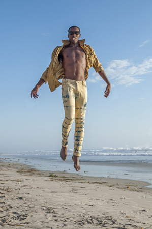 american sexy: Fashionable sexy African American man leaps high in air on beach and appears to fly away Stock Photo