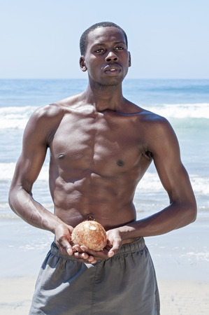 nude abs: Handsome fit lean African American man stands shirtless on beach while holding fresh coconut