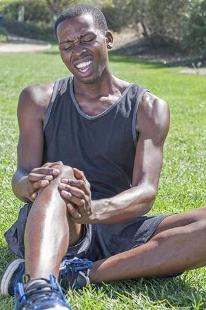 piernas hombre: Joven atleta afroamericano magra en pantalones cortos y camisetas sin mangas se sienta en la hierba embrague lesionado de la rodilla y que muestra la expresi�n facial dolorosa