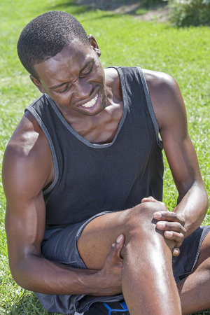 knee cap: Young lean African American athlete in shorts and tank top sits on grass clutching injured knee and showing painful facial expression