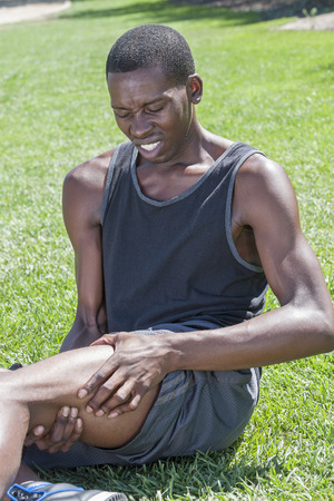 hamstring: Young lean African American male athlete sits on grass clutching injured leg and hamstring while in excruciating pain