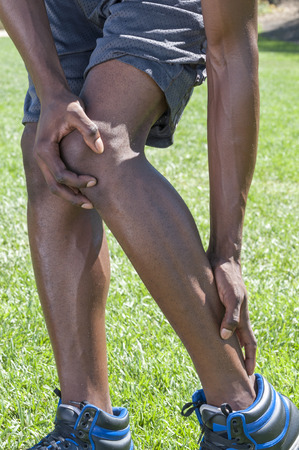 Closeup of lean muscular African American male runner massaging injured leg suffering from Achilles tendonitis as he stands in shorts on green lawn photo