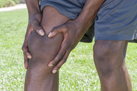leg injury: Closeup of knee and leg of lean African American male athlete clutching injured knee with fingers around the patella on green lawn outdoors