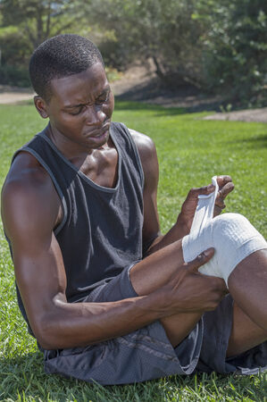 Lean muscular African American male athlete in shorts and tank top wraps injured knee with white sports bandage while sitting on grass Stock fotó