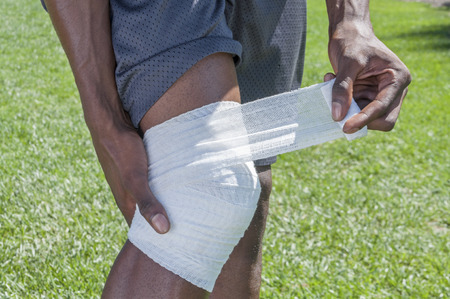 Closeup of lean fit African American man wrapping injured knee with white sports bandage while standing on grass Stock Photo