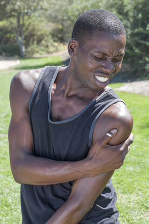 Lean muscular African American man in black tank top in park holds deltoid muscle afflicted by painful injury with agonized expression on face