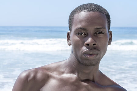 Closeup portrait of sexy and handsome young African American man shirtless on sunny beach in summer photo