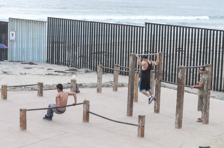 TIJUANA, MEXICO - JULY 26, 2014: Exercise enthusiasts workout with outdoor exercise equipment on the beach in Tijuana, Mexico along the border fence that separates the U.S. and Mexico