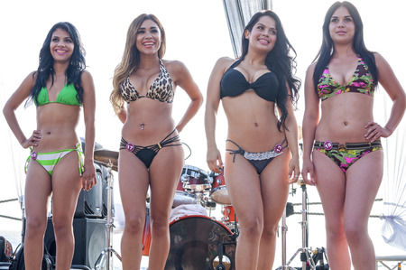 TIJUANA, MEXICO - JULY 27, 2014:  Four beautiful Latin women wait for judges final decision on stage at the bikini contest of the 6th annual beach festival in Playas de Tijuana, Mexico. Editorial