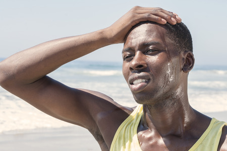Young sweaty lean African American man outdoors in tank top places hand on forehead and expresses disappointment photo