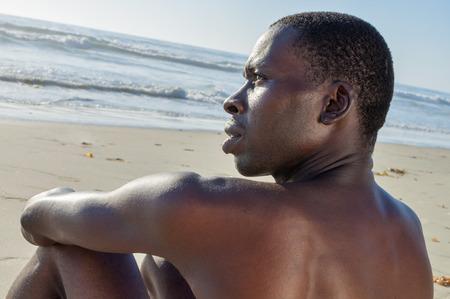 nue plage: Gros plan de profil torse nu maigre homme afro-américain avec une expression intense assis et de penser sur la plage de sable Banque d'images