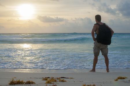 Adventurous Caucasian hiker stands on beautiful Caribbean beach observing a glorious sunrise