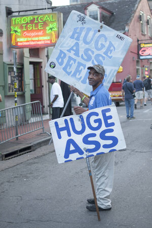 bourbon street: NEW ORLEANS, USA - OCTOBER 10, 2014: Beer promoter carries \Huge Ass Beer\ signs on Bourbon Street in New Orleans. Editorial