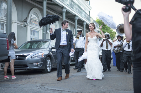 procession: NEW ORLEANS, USA - OCTOBER 10, 2014: Happily newly wed bride and groom parade through the streets of the French Quarter in New Orleans followed by a jazz band in celebration of their union.