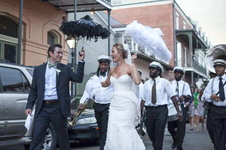 wedding bands: NEW ORLEANS, USA - OCTOBER 10, 2014: Newly wed bride and groom parade through the streets of the French Quarter in New Orleans followed by a jazz band in celebration of their union.