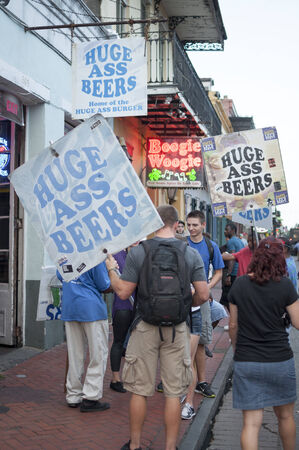 bourbon street: NEW ORLEANS, USA - OCTOBER 10, 2014: Beer promoters carry \Huge Ass Beer\ signs and urge tourists to enter the bar of the same name on Bourbon Street. Editorial