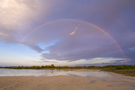 extends: Beautiful rainbow extends over the island of Isla Blanca and Chacmuchuc Lagoon near Cancun, Mexico