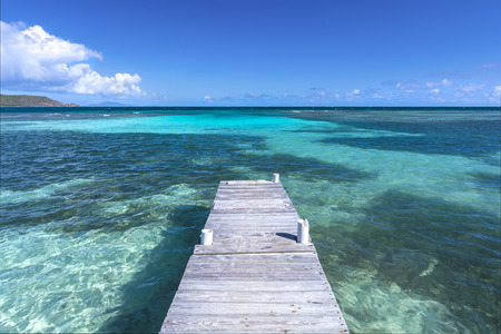 extends: Rustic wooden dock extends into clear shallow lagoon at Playa Larga beach on Caribbean island of Isla Culebra in Puerto Rico