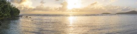 linda: Wide panoramic of sun setting behind clouds over Caribbean Sea and beach of Bahia Linda on Isla Culebra
