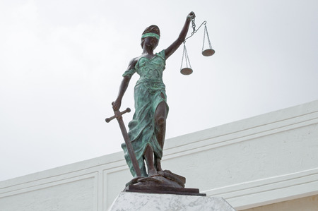 Beautiful bronze statue of Lady Justice blindfolded holding balancing scales in one hand and sword in other in Chetumal, Mexico