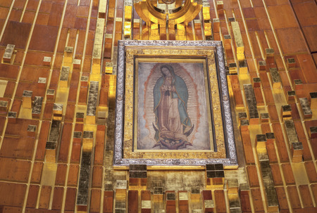 shrine: MEXICO CITY, MEXICO - OCT0BER 23, 2014: The original tilma hangs framed behind glass in a shrine behind the altar of the new Basilica of Our Lady of Guadalupe in Mexico City