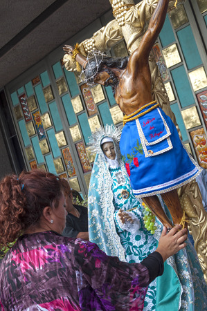 MEXICO CITY, MEXICO - OCTOBER 23, 2014: A woman touches the feet of a statue of Christ on the cross standing next to a statue of the Holy Mother at the Basilica of Our Lady of Guadalupe.