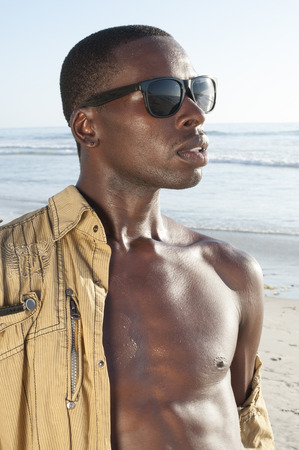 Portrait of handsome sexy African American man with unbuttoned shirt and shades on sunny beach photo