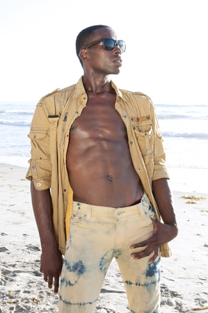 american sexy: Sexy African American model with unbuttoned shirt and wearing jeans and dark shades on sunny beach Stock Photo
