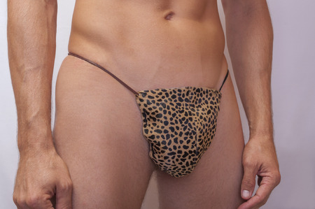 Frontal closeup of sexy lean Caucasian man wearing cheetah fur pouch thong with leather stings on gray background