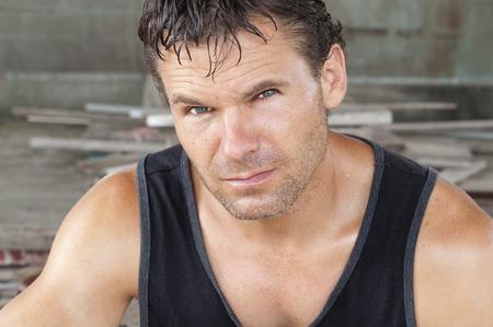 rugged: Closeup portrait of unshaven sweaty Caucasian man in black tank top working in construction area