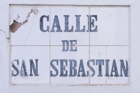 weather beaten: Il tempo pesantemente battuto marcatore strada tegola identificare Calle de San Sebastian in Old San Juan, Puerto Rico