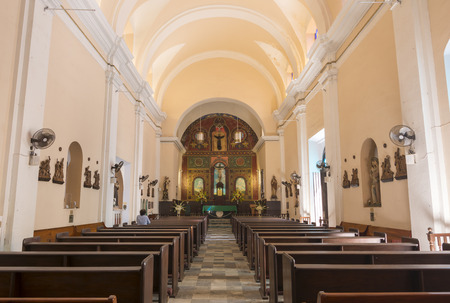 pews: Interior of Cathedral of San Juan Bautista in Old San Juan, Puerto Rico showing altar and wooden pews with one faithful worshiper