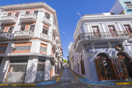 san juan: SAN JUAN, PUERTO RICO - JANUARY 29, 2014: Narrow brick streets and historical colonial-style architecture like these buildings on Calle San Francisco and Calle O