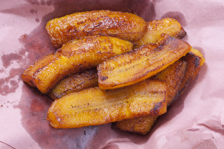 Sliced greasy fried plantain bananas on pink paper to soak up excess grease Standard-Bild