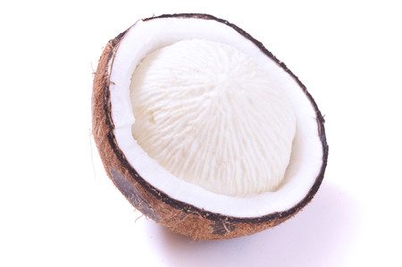 spongy: Cracked open sprouted coconut with spongy grooved white meat on white background Stock Photo