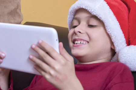 he laughs: Cute young boy in Santa hat laughs as he plays with his tablet at home while lying on couch