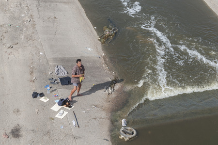 hard times: TIJUANA, MEXICO - NOVEMBER 13, 2014: A homeless man with his belongings laid out on concrete river bank dries his clothes as he stands in his boxers and with a bandaged ankle along the heavily contaminated Tijuana River