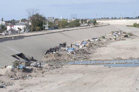 pitched: TIJUANA, MEXICO - NOVEMBER 13, 2014: Growing homeless camps of pitched tents and garbage are a sad sight seen from the pedestrian bridge that crosses the Tijuana River flood channel