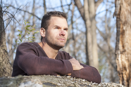 deep thought: Scruffy handsome Caucasian man with arms crossed leaning over fallen log in thick wooded area stares off into distance in deep thought