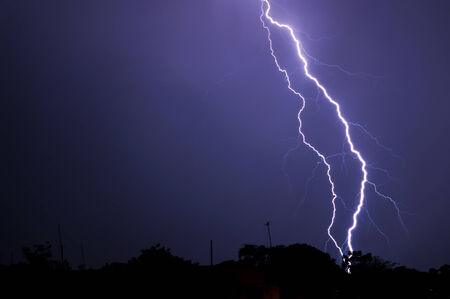 electrifying: Dark silhouette of town as intense electrifying lightning bolt strikes the ground Stock Photo