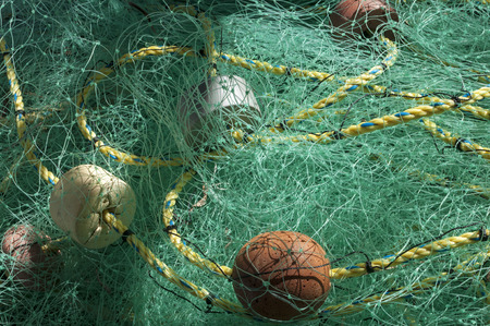 buoys: Artistic shadows on pile of monofilament fishing net with rope and buoys